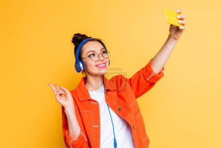 Photo for Cheerful student in headphones taking selfie on smartphone while showing victory gesture isolated on yellow - Royalty Free Image