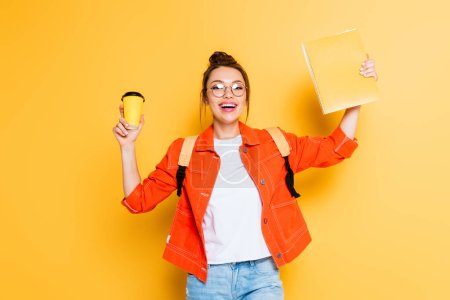 Photo pour Excited student holding coffee to go and copy book in raised hands while smiling at camera on yellow background - image libre de droit