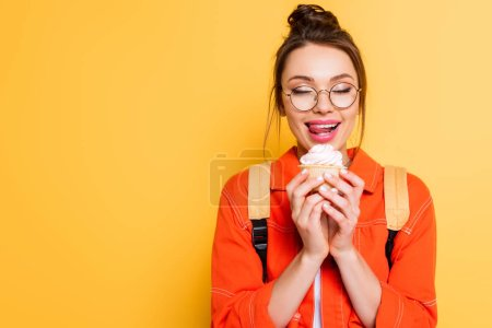 Photo pour Happy student with closed eyes sticking her lips while holding delicious cupcake on yellow background - image libre de droit