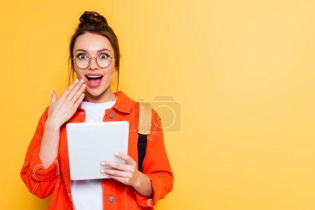 Photo pour Étudiant choqué tenant la main près de la bouche tout en tenant comprimé numérique isolé sur jaune - image libre de droit