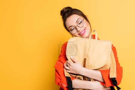 Photo pour Étudiant heureux dans des lunettes tenant sac à dos avec les yeux fermés sur fond jaune - image libre de droit