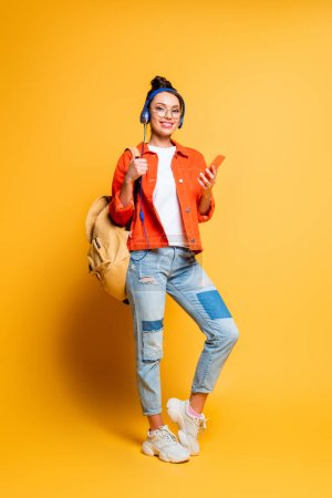 attractive smiling student in headphones holding backpack and smartphone while looking at camera on yellow background