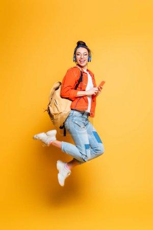 Foto de Estudiante excitado en audífonos y gafas saltando mientras mantiene el teléfono inteligente en el fondo amarillo. - Imagen libre de derechos