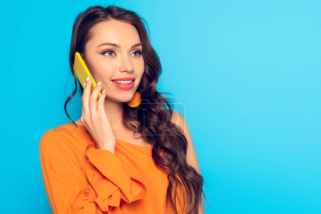 Photo for Beautiful, elegant girl talking on smartphone and smiling while looking away isolated on blue - Royalty Free Image