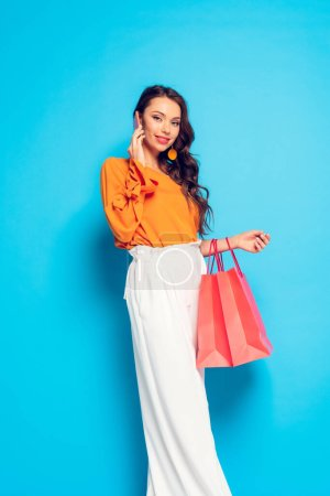Photo for Attractive fashionable girl talking on smartphone while holding shopping bags on blue background - Royalty Free Image