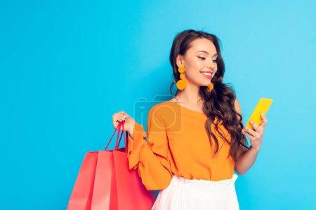 alegre elegante chica sosteniendo bolsas de compras mientras chatea en el teléfono inteligente sobre fondo azul