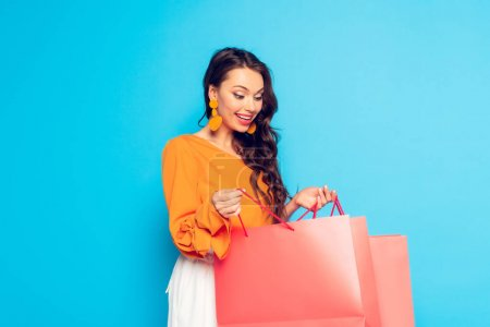 attractive excited girl looking into shopping bag on blue background