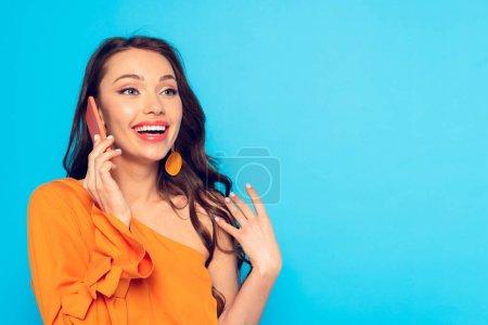 Photo pour Joyeuse fille à la mode parlant sur smartphone tout en regardant loin isolé sur bleu - image libre de droit