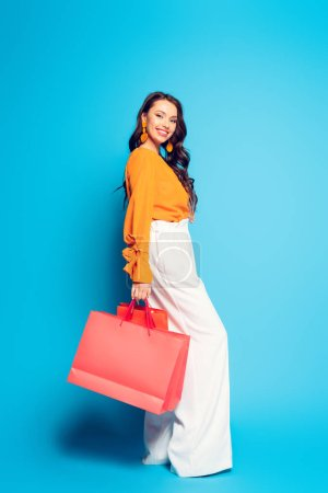 Photo for Smiling fashionable girl holding shopping bags and looking at camera on blue background - Royalty Free Image