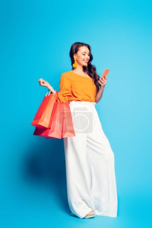 Photo for Cheerful stylish woman chatting on smartphone while holding shopping bags on blue background - Royalty Free Image