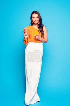 Photo pour Attrayant femme à la mode bavarder sur smartphone tout en tenant café pour aller et sourire à la caméra sur fond bleu - image libre de droit