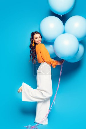Photo for Full length view of happy stylish woman standing on one leg while holding big festive balloons on blue background - Royalty Free Image