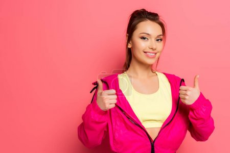 Photo for Young cheerful sportswoman showing thumbs up while smiling at camera on pink background - Royalty Free Image