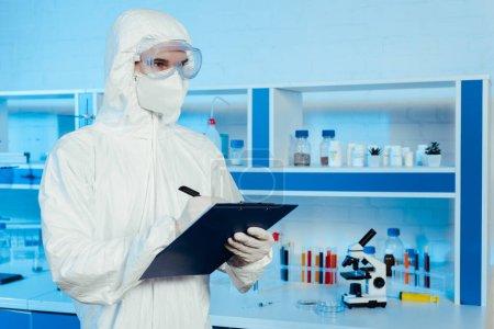Photo pour Scientifique en combinaison Hazmat et lunettes tenant presse-papiers et stylo près du microscope - image libre de droit