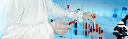 Photo for Panoramic shot of scientist in latex gloves holding syringe near test tubes - Royalty Free Image