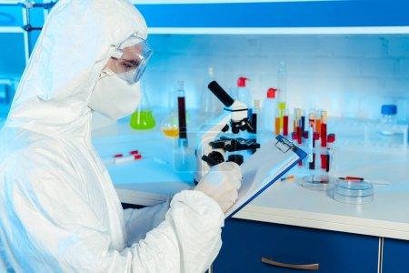 Photo pour Scientifique en combinaison Hazmat et lunettes écriture près du microscope - image libre de droit