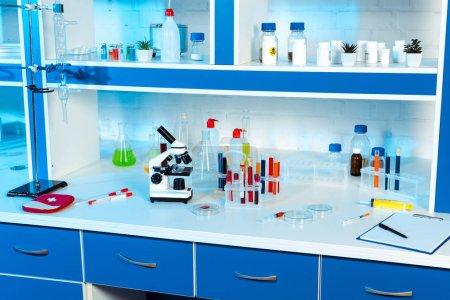 Photo pour Flacons, éprouvettes et flacons près du microscope dans un laboratoire moderne - image libre de droit