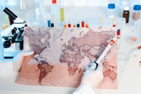 Photo pour View croisée d'un scientifique tenant un échantillon avec lettrage coronavirus près de la carte - image libre de droit