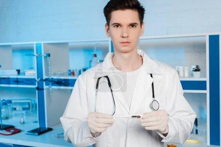 Photo pour Beau scientifique dans des gants de latex tenant un thermomètre numérique - image libre de droit