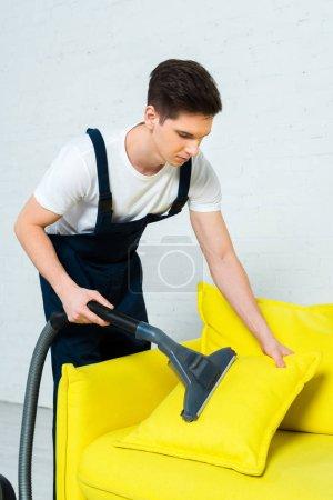 Photo pour Beau nettoyeur en salopette enlever la poussière sur l'oreiller avec aspirateur - image libre de droit