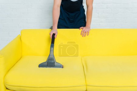 Photo pour Cropped view of man in uniform removing dust on sofa with vacuum cleaner - image libre de droit