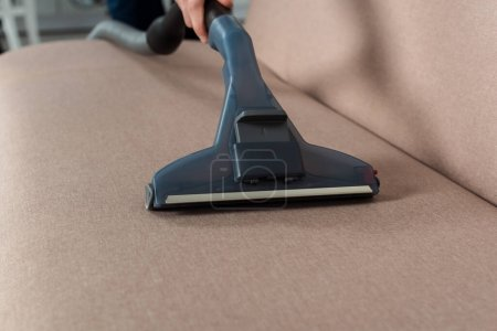 Photo for Cropped view of man dry cleaning modern sofa with vacuum cleaner - Royalty Free Image
