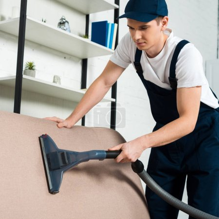 young handsome cleaner in cap removing dust on sofa with vacuum cleaner