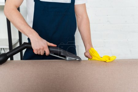 Photo for Cropped view of man cleaning sofa with vacuum cleaner and cleaning cloth - Royalty Free Image
