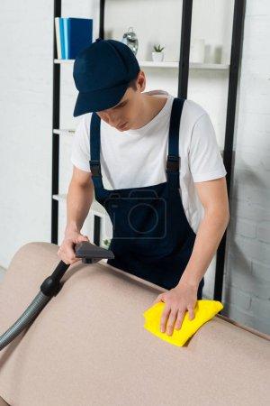 Photo pour Homme en casquette et salopette canapé nettoyant avec aspirateur et chiffon nettoyant - image libre de droit