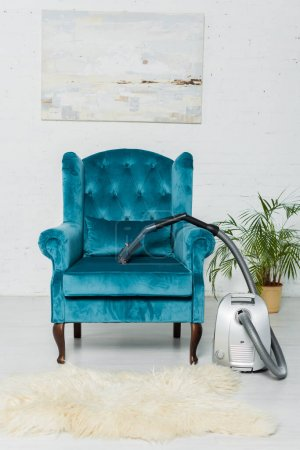 Photo for Vacuum cleaner on carpet near modern armchair in living room - Royalty Free Image