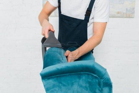 Photo pour Vue recadrée du nettoyeur en salopette nettoyage à sec fauteuil moderne avec aspirateur - image libre de droit
