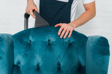 cropped view of cleaner dry cleaning blue modern armchair with vacuum cleaner