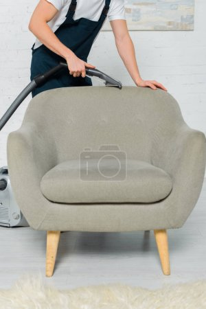 Photo for Cropped view of cleaner in uniform dry cleaning armchair with vacuum cleaner - Royalty Free Image