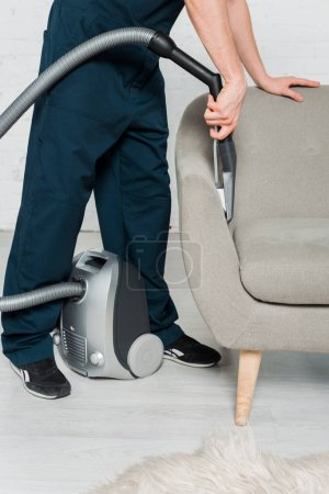 Photo for Cropped view of young cleaner in uniform dry cleaning armchair with vacuum in modern living room - Royalty Free Image