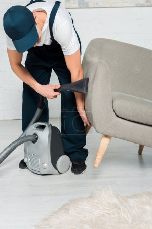 Photo for Cleaner in uniform and cap washing armchair with vacuum in modern living room - Royalty Free Image