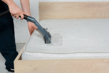 Photo for Cropped view of cleaner holding vacuum cleaner while cleaning mattress - Royalty Free Image