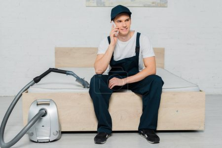 Photo pour Happy cleaner in cap sitting on bed and talking on smartphone near vacuum cleaner - image libre de droit