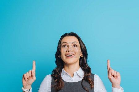 Photo pour Une femme d'affaires surprise regarde vers le haut et pointe du doigt, les doigts isolés sur le bleu - image libre de droit