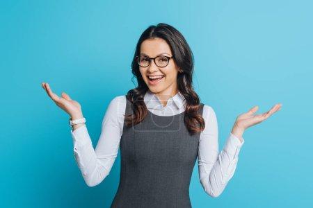 Photo pour Une femme d'affaires excitée sourit à la caméra alors qu'elle se tient les bras ouverts sur fond bleu - image libre de droit