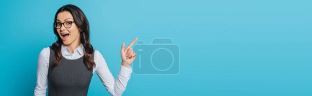 Photo for Panoramic shot of amazed businesswoman in eyeglasses pointing with finger isolated on blue - Royalty Free Image