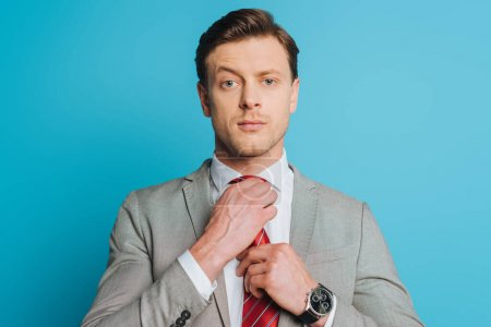 Photo for Handsome, confident businessman touching tie while looking at camera isolated on blue - Royalty Free Image
