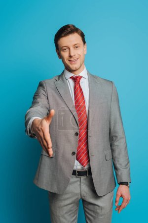 Photo for Smiling businessman showing greeting gesture with outstretched hand while looking at camera on blue background - Royalty Free Image