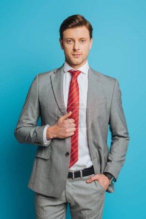 Photo pour Bel homme d'affaires confiant debout avec la main dans la poche et regardant la caméra sur fond bleu - image libre de droit
