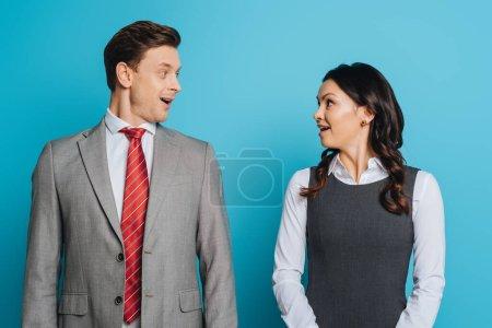 Foto de Dos empresarios sorprendidos mirándose unos a otros en un fondo azul - Imagen libre de derechos