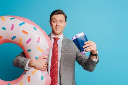 Photo pour Homme d'affaires joyeux avec anneau de natation montrant passeports et billets d'avion sur fond bleu - image libre de droit