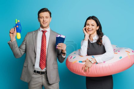 Photo pour Homme d'affaires souriant tenant passeports, billets d'avion et pistolet à eau près de joyeuse femme d'affaires en anneau de natation sur fond bleu - image libre de droit