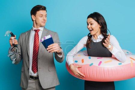 Photo pour Femme d'affaires excitée dans l'anneau de natation regardant homme d'affaires tenant passeports, billets d'avion et masque de plongée sur fond bleu - image libre de droit