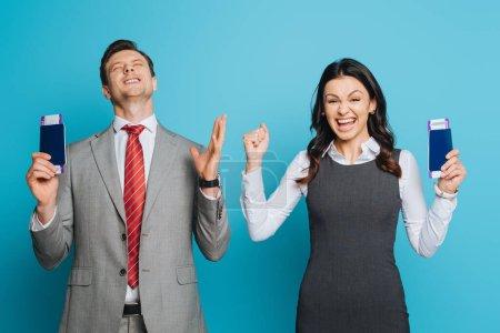 Photo pour Deux hommes d'affaires enthousiastes montrant des gestes de vainqueur tout en tenant des passeports et des billets d'avion sur fond bleu - image libre de droit