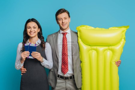 Photo for Smiling businessman holding inflatable mattress and hugging businesswoman showing passports and air tickets isolated on blue - Royalty Free Image