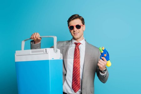 Photo for Happy businessman in sunglasses holding portable fridge and water gun on blue background - Royalty Free Image